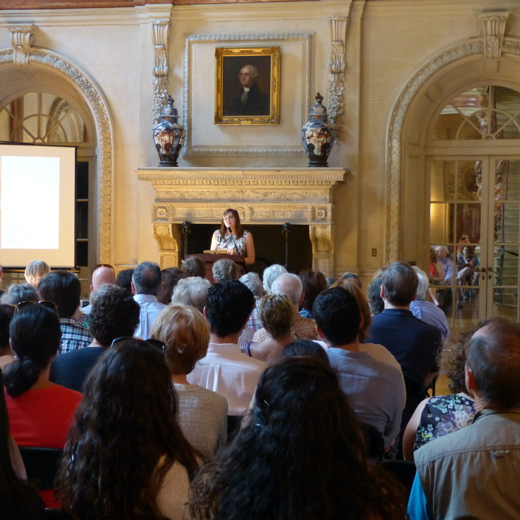 Image of Curator Emily Parsons speaking to an audience at a public program in the Ballroom of Anderson House.