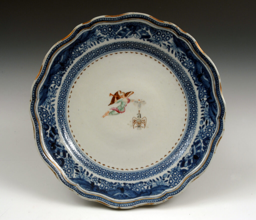 Society of the Cincinnati porcelain dinner plate with blue border and winged female figure holding a trumpet and eagle-shaped medal suspended from a ribbon